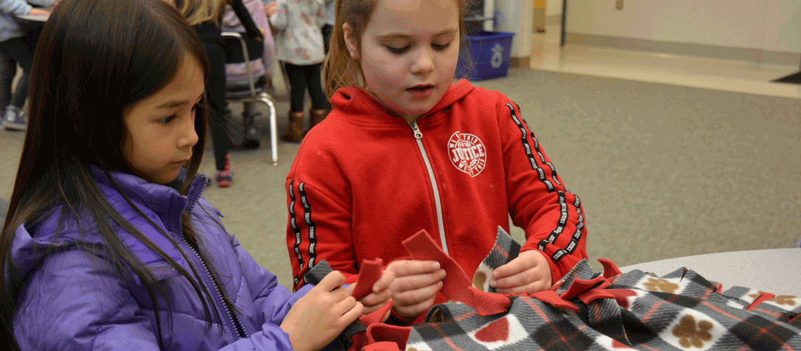 Two students tie knots in the edge of a blanket they are making, seated at a table