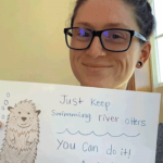 Staff member with sign saying Just keep Swimming Otters, you can do it