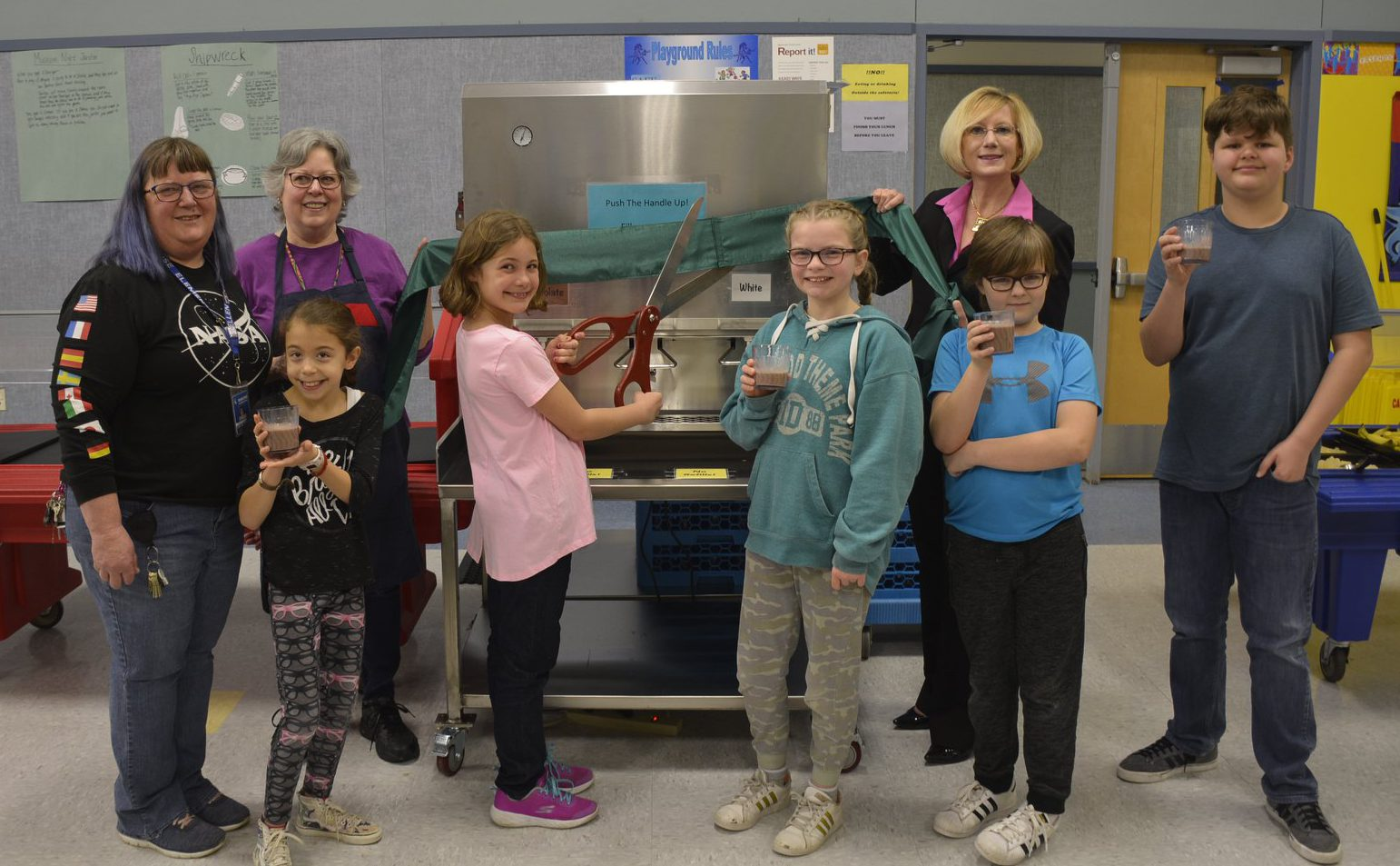 Members of the Gause Green Team, food service team, and students welcome the new milk dispenser to the school cafeteria, posing with cups of regular or chocolate milk.