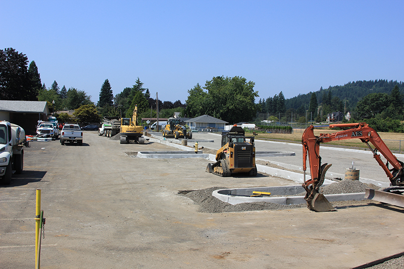 Construction equipment prepping surface for paving in north parking lot, showing various excavators and loaders