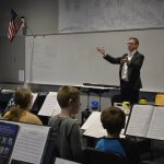 Guest conductor working with students in the JMS band, with students looking at sheet music on stands