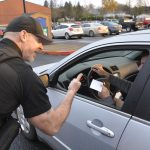 Washougal Police Officer gives thumbs up to teen driver for wearing seatbelt, and provides gift card to student driving car