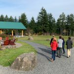 Group of students touring the campus of the Skamania Lodge with trees and event gazebo in the background