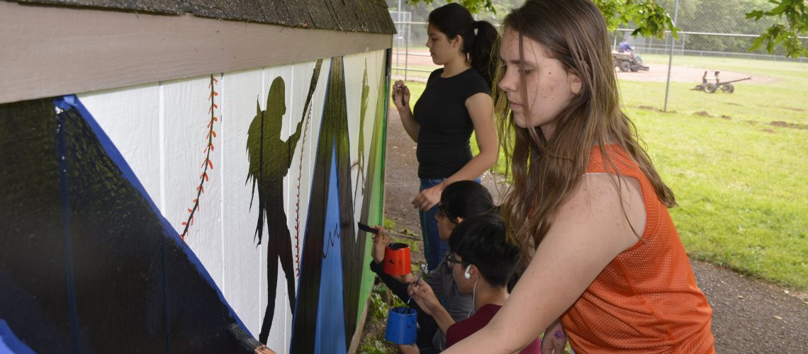 Student adding detail to Hathaway park mural