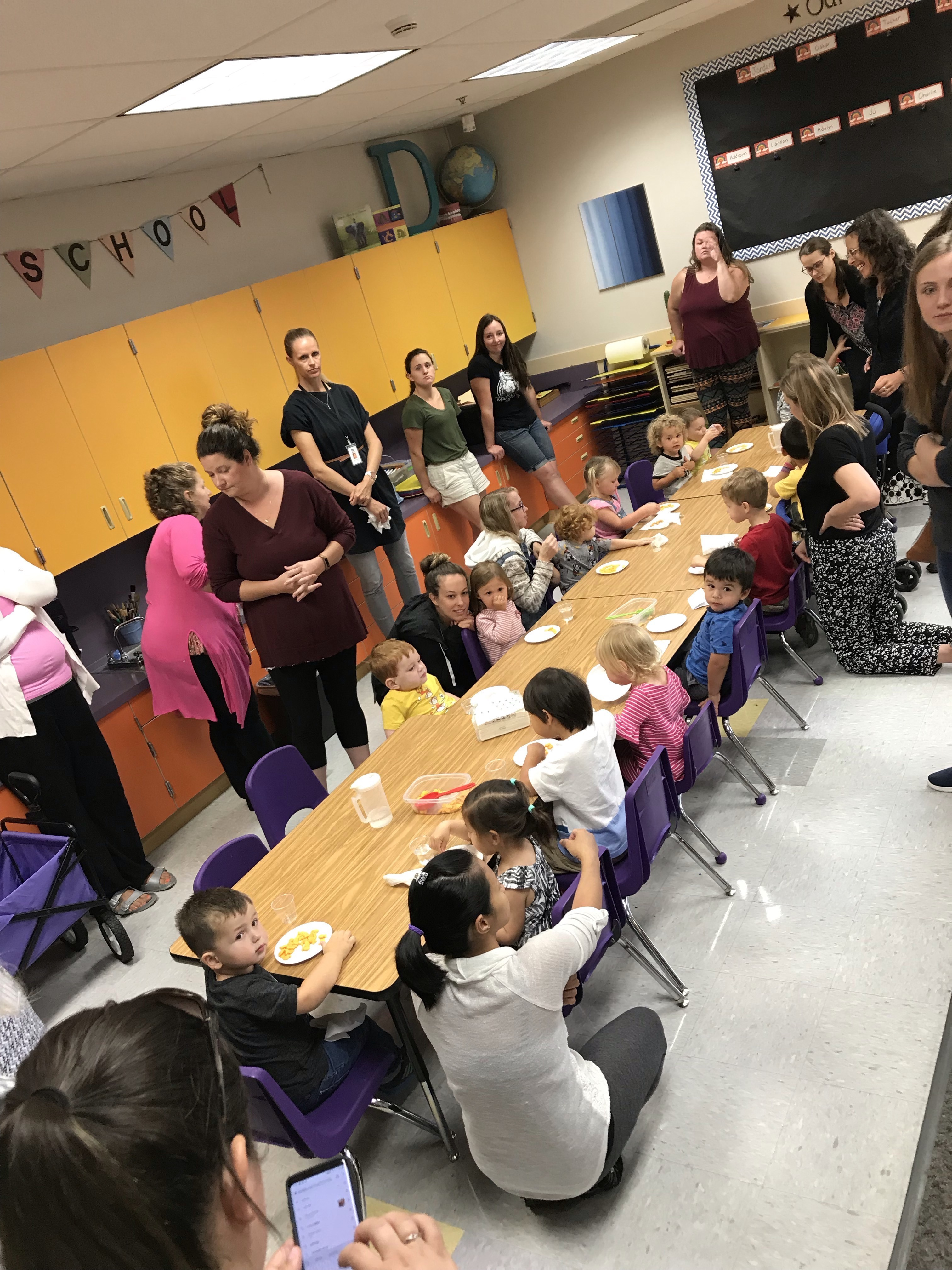 1-2-3 grow preschool students seated at a table with parents and staff across from them