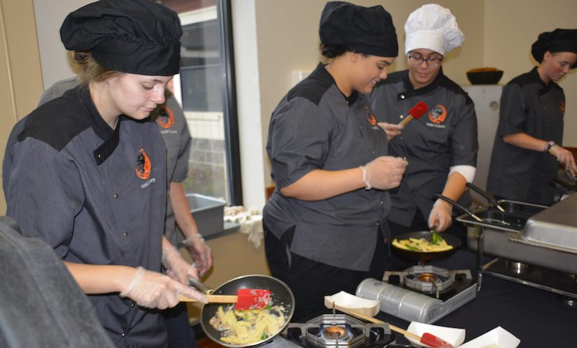 WHS Culinary students cooking pasta on a table in commons, and putting it onto plates