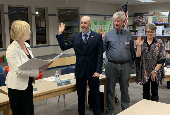 Superintendent Mary Templeton administers the oath of office for board member Cory Chase, Jim Cooper, and Angela Hancock in the Gause Library