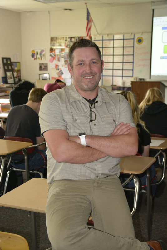Jim Reed poses on a desk in his classroom with students working in the background