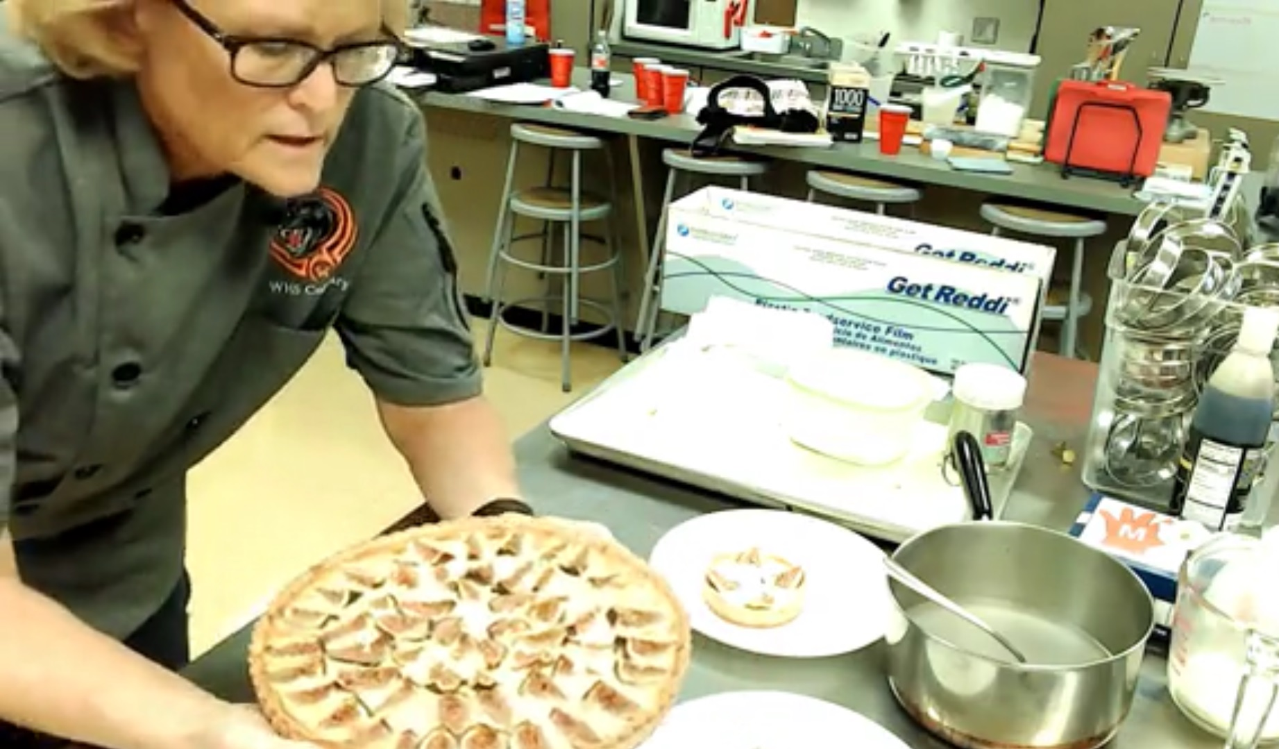 Brenda working on a fig tart, with ingredients on the prep surface behind and around her